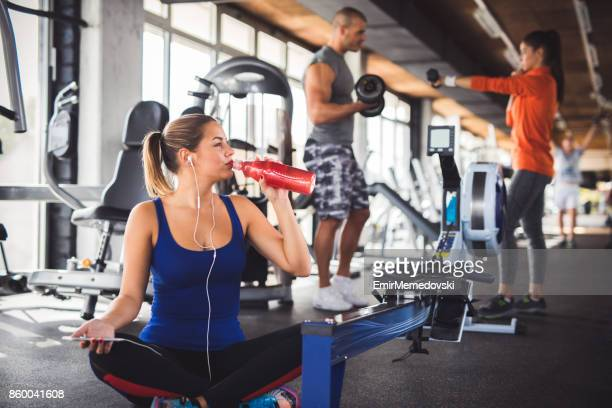 Junge Frau trinkt Erfrischungsgetränk nach Training im Fitness-Studio