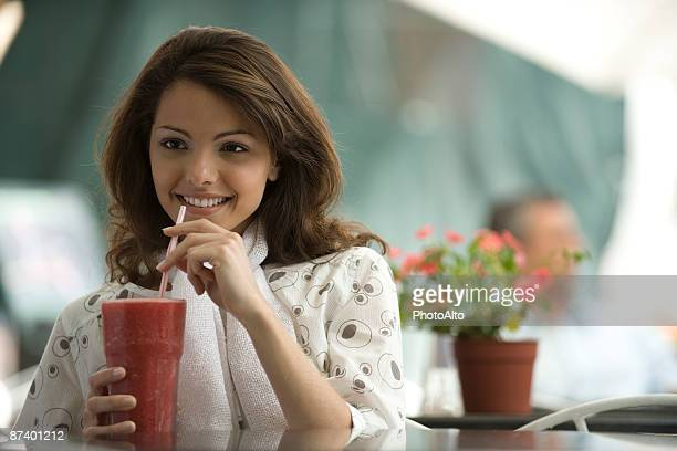 Young woman drinking smoothie in sidewalk cafe