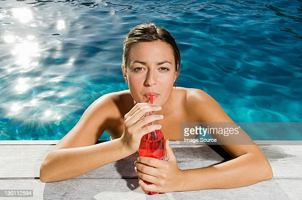 Young woman drinking soft drink at poolside