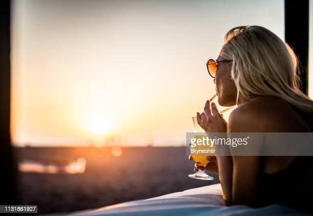 jonge vrouw drinken zomer cocktail op het strand bed bij zonsondergang. - koude dranken stockfoto's en -beelden