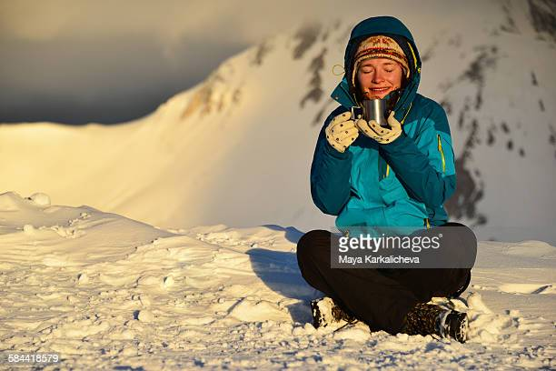 Young woman drinking tea at snowy mountain ridge