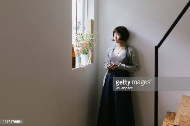 young woman drinking tea by the window - avoidance stock pictures, royalty-free photos & images