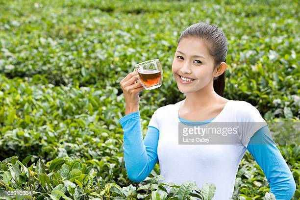 Young Woman Drinking Tea in a Tea Field