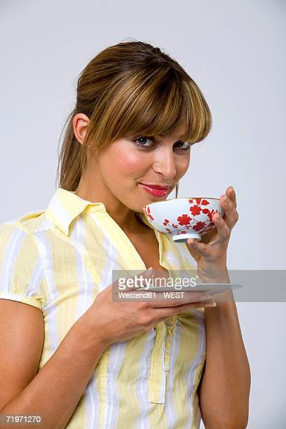 Young woman drinking tea, portrait, close-up