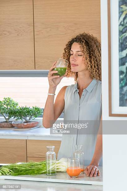Young woman drinking vegetable juice in the kitchen