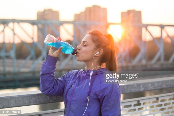 young woman drinking vitamin water - energy drink stock pictures, royalty-free photos & images