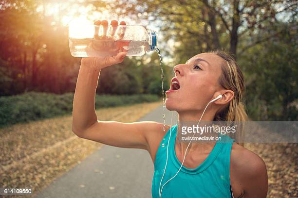 Young woman drinking water after jogging outdoors