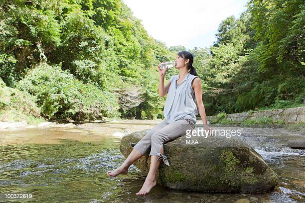 Young Woman Drinking Water at River