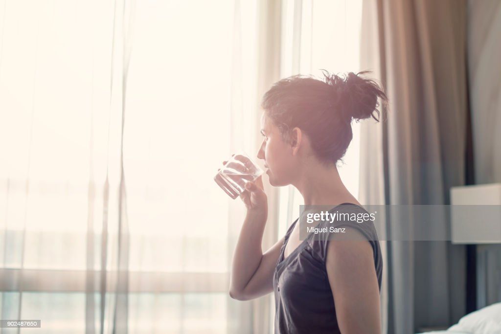 Young woman drinking water in the bedroom : Stock Photo