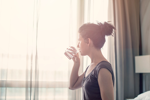 Young woman drinking water in the bedroom - gettyimageskorea