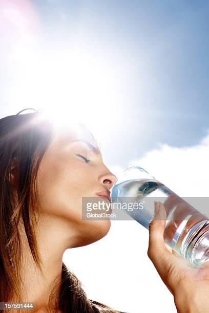 Junge Frau Trinkwasser auf einem sonnigen Tag