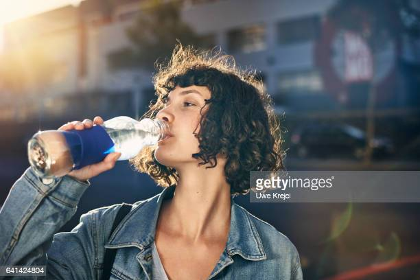 young woman drinking water out of glass bottle - boire photos et images de collection