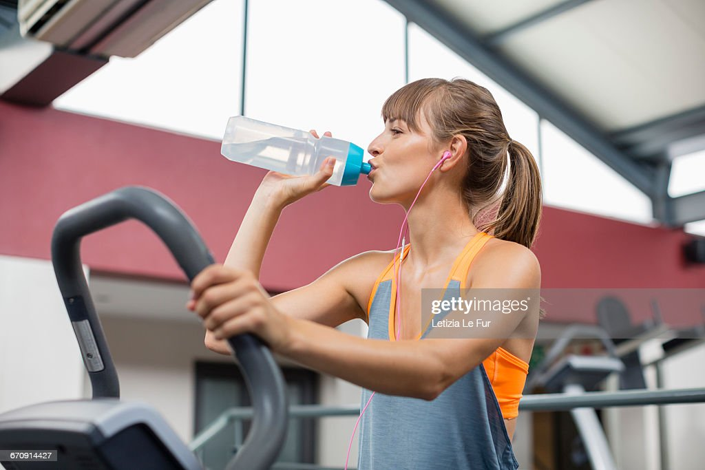 Young woman drinking water while exercising on a machine in gym young woman drinking water while exercising on a machine in gym stock photo sciox Choice Image