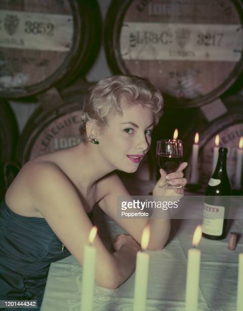 A young woman drinks a glass of red wine at a table illuminated by candlelight at a wine bar in 1957 Wine barrels are stacked up on the wall behind...