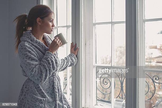 Young woman drinks morning coffee, looking through the window