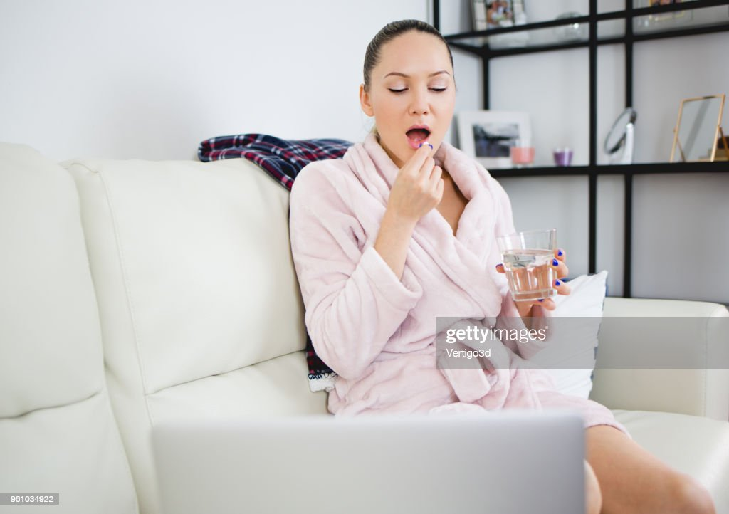 Young woman drinks pills she think about her health : Stock Photo
