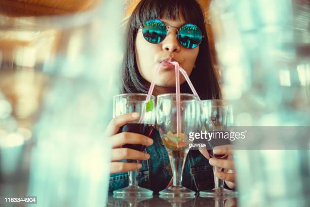young woman drinks three glass of mock-tail at once. - lemon soda stock pictures, royalty-free photos & images