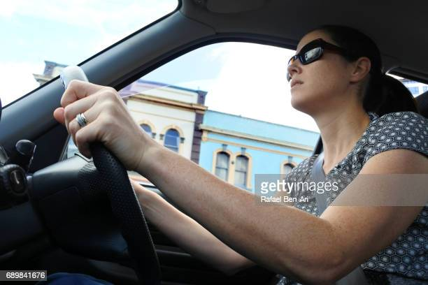 young woman drives a car - rafael ben ari stock-fotos und bilder