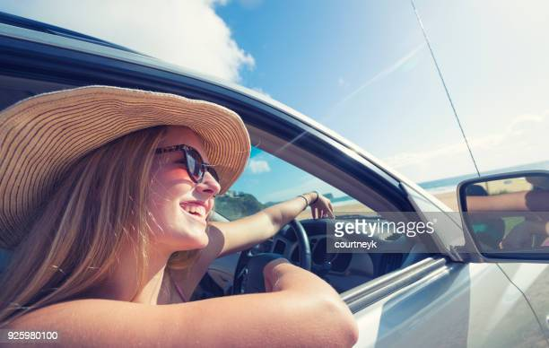 jovem mulher dirigindo um carro na praia. - aluguel de carro - fotografias e filmes do acervo