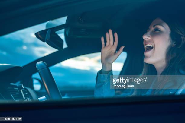 young woman driving a car - singing stock pictures, royalty-free photos & images