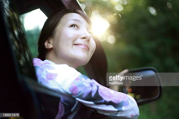 young woman driving a car,yukata - landfahrzeug stock-fotos und bilder