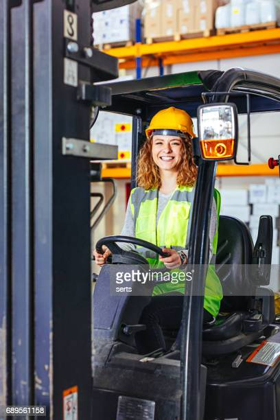 Young woman driving a forklift at warehouse