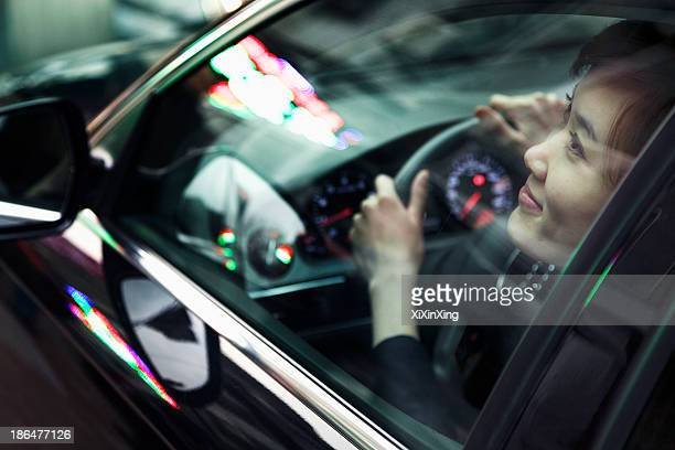 Young woman driving and looking through car window at the city night lights