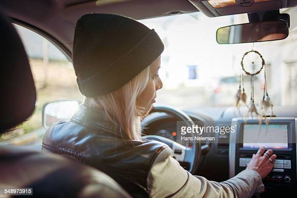 Young woman driving and using GPS system in car