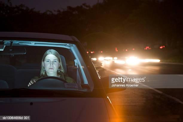 Young woman driving car at night
