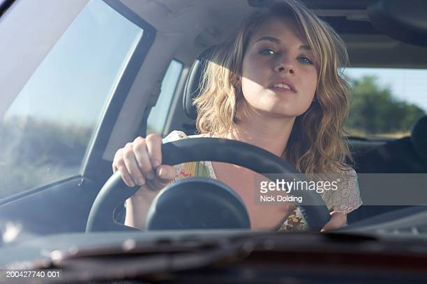 Young woman driving car, close-up, view through windscreen