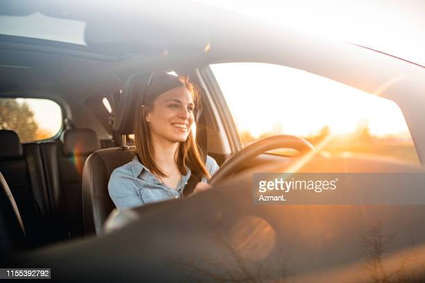 young woman driving car on a sunny day - car stock pictures, royalty-free photos & images