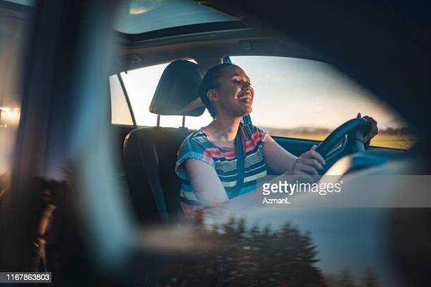 young woman driving car on a sunny day - singing stock pictures, royalty-free photos & images