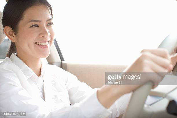 Young woman driving car, smiling