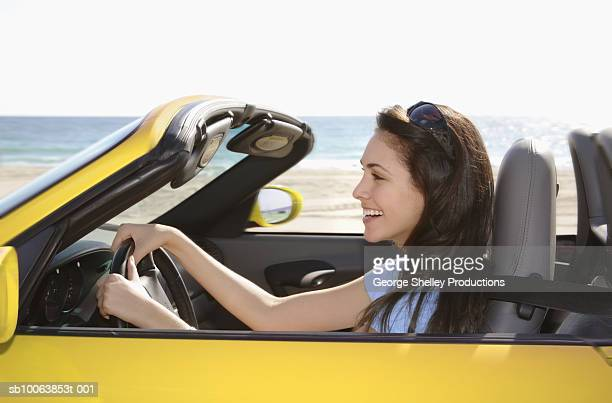 young woman driving yellow convertible, side view - convertible stock pictures, royalty-free photos & images
