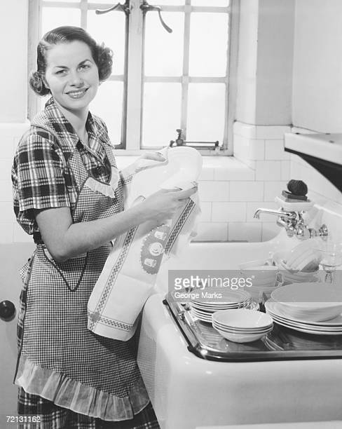 Young woman drying dishes in kitchen (B&W), portrait
