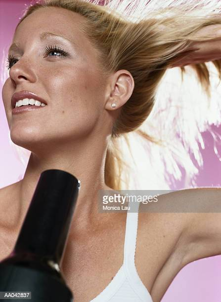 young woman drying hair - blow drying hair stock pictures, royalty-free photos & images