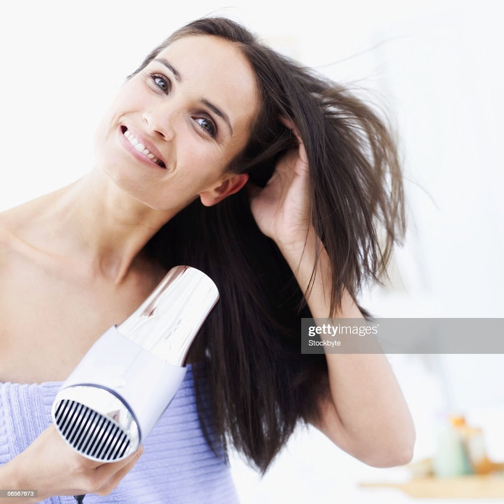 young woman drying her hair with a hair dryer : Stock Photo