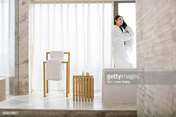 Young woman drying her hair with a towel in bathroom