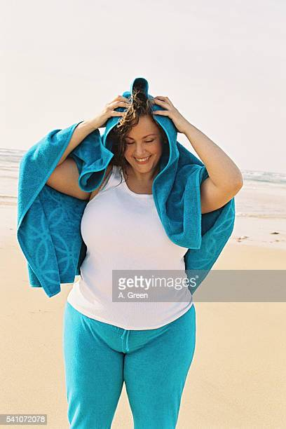 young woman drying her hair with towel on the beach - dicke frauen am strand stock-fotos und bilder