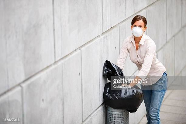 Young woman dumping garbage in dustbin