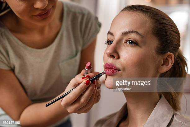 Young woman during make-up treatment.