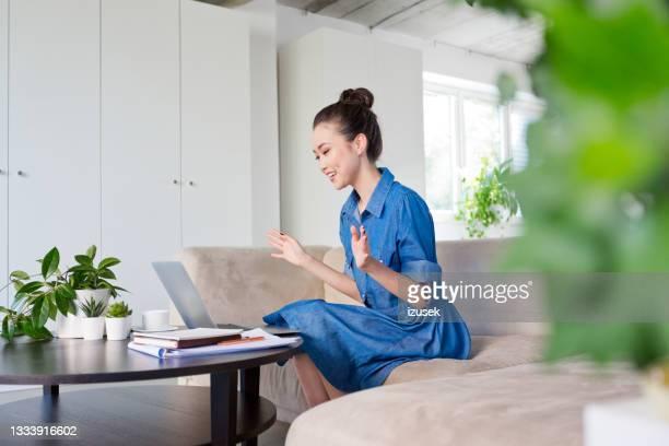 mujer joven durante videollamada en la oficina - izusek fotografías e imágenes de stock