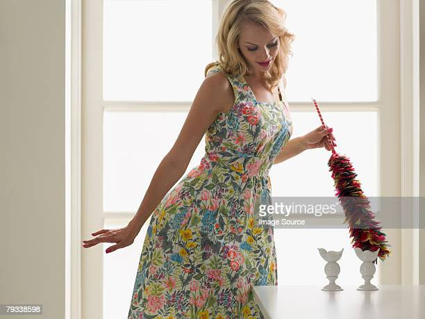 Young woman dusting ornaments