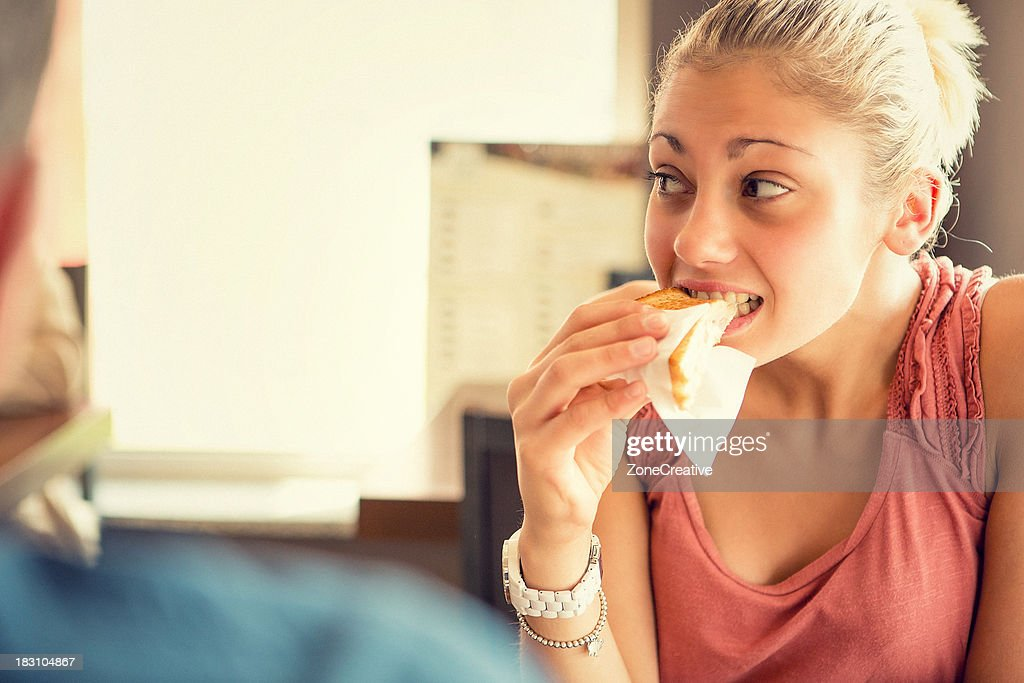 Young woman eat a toast at italian café : Photo