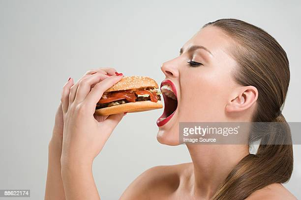 young woman eating a burger - ハンバーガー ストックフォトと画像