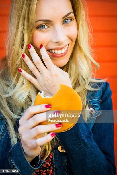 Joven mujer comiendo una burguer