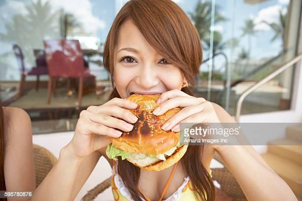Young woman eating a hamburger, Guam, USA