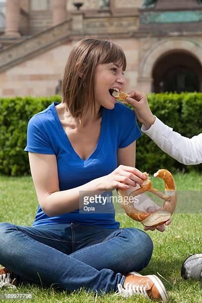 Joven mujer comiendo una Pretzel