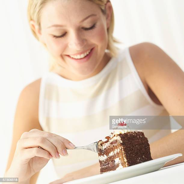 Young woman eating a slice of cake with a fork