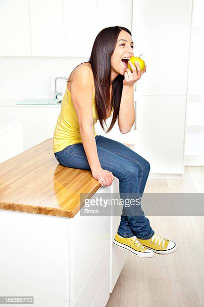 Young woman eating an apple on a modern kitchen